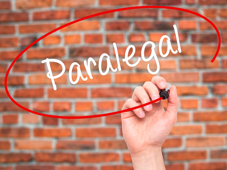 paralegal: Man Hand writing Paralegal with black marker on visual screen. Isolated on bricks. Business, technology, internet concept. Stock Photo