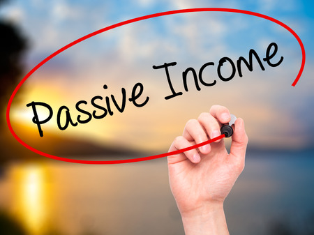 passive income: Man Hand writing Passive Income with black marker on visual screen. Isolated on nature. Business, technology, internet concept. Stock Photo Stock Photo