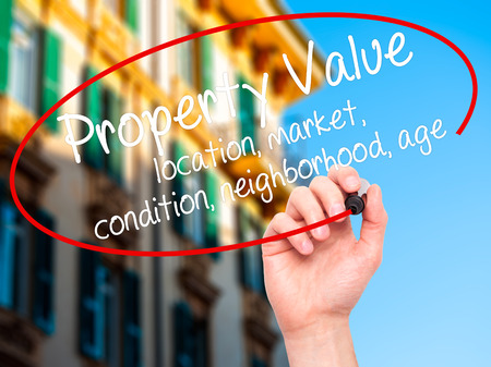 Man Hand writing Property Value - location, market, condition, neighborhood, age with black marker on visual screen. Isolated on city. Business, technology, internet concept. Stock Image