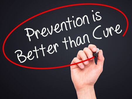 cure prevention: Man Hand writing Prevention is Better than Cure with black marker on visual screen. Isolated on black. Business, technology, internet concept. Stock Photo