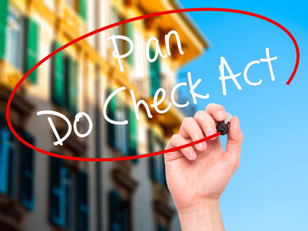 plan do check act: Man Hand writing Plan Do Check Act  with black marker on visual screen. Isolated on city. Business, technology, internet concept. Stock Photo Stock Photo