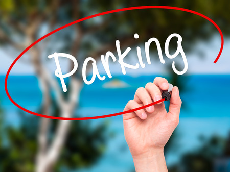 writing on screen: Man Hand writing Parking with black marker on visual screen. Isolated on nature. Business, technology, internet concept. Stock Photo