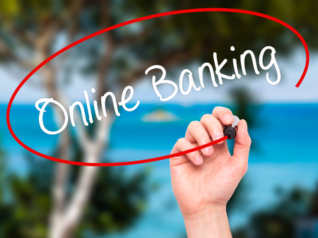 e banking: Man Hand writing Online Banking with black marker on visual screen. Isolated on background. Business, technology, internet concept. Stock Photo Stock Photo