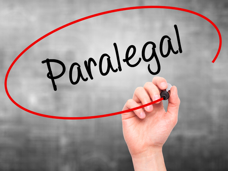 paralegal: Man Hand writing Paralegal with black marker on visual screen. Isolated on grey. Business, technology, internet concept. Stock Photo