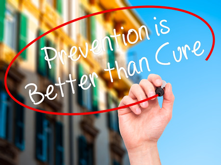 cure prevention: Man Hand writing Prevention is Better than Cure with black marker on visual screen. Isolated on city. Business, technology, internet concept. Stock Photo