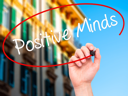 open minded: Man Hand writing Positive Minds with black marker on visual screen. Isolated on city. Business, technology, internet concept. Stock Photo Stock Photo
