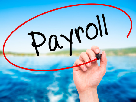 payroll: Man Hand writing Payroll with black marker on visual screen. Isolated on nature. Business, technology, internet concept. Stock Photo