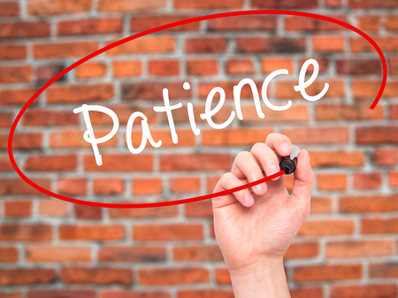 paciencia: Hombre de la mano escribiendo paciencia con marcador negro en la pantalla visual. Aislado en el fondo. Negocios, la tecnolog�a, el concepto de internet. Foto de stock Foto de archivo