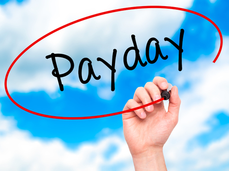 monthly salary: Man Hand writing Payday with black marker on visual screen. Isolated on sky. Business, technology, internet concept. Stock Photo