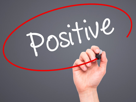 positiveness: Man Hand writing Positive with black marker on visual screen. Isolated on background. Business, technology, internet concept. Stock Photo