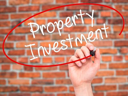press agent: Man Hand writing Property Investment with black marker on visual screen. Isolated on bricks. Business, technology, internet concept. Stock Photo
