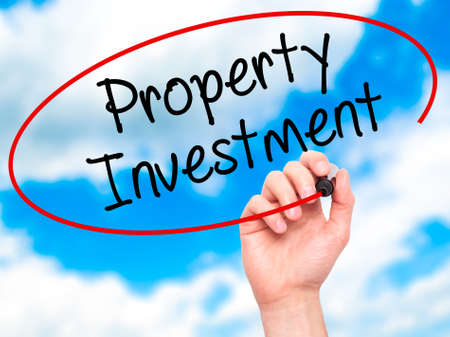 press agent: Man Hand writing Property Investment with black marker on visual screen. Isolated on sky. Business, technology, internet concept. Stock Photo