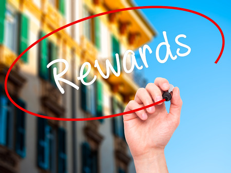 payoff: Man Hand writing Rewards with black marker on visual screen. Isolated on city. Business, technology, internet concept. Stock Photo Stock Photo