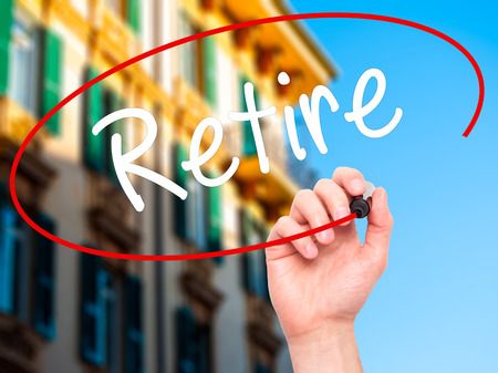retire: Man Hand writing Retire with black marker on visual screen. Isolated on background. Business, technology, internet concept. Stock Photo Stock Photo