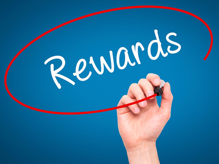 eminence: Man Hand writing Rewards with black marker on visual screen. Isolated on blue. Business, technology, internet concept. Stock Photo