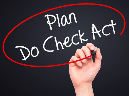 plan do check act: Man Hand writing Plan Do Check Act  with black marker on visual screen. Isolated on black. Business, technology, internet concept. Stock Photo