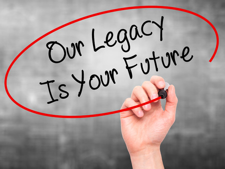 legacy: Man Hand writing Our Legacy Is Your Future  with black marker on visual screen. Isolated on background. Business, technology, internet concept. Stock Photo