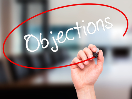 objections: Man Hand writing Objections  with black marker on visual screen. Isolated on office. Business, technology, internet concept. Stock Photo