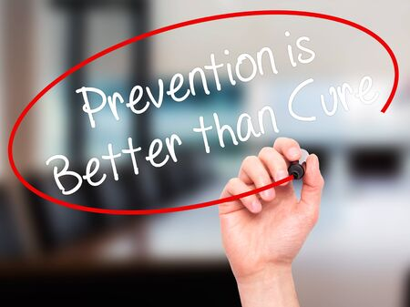 cure prevention: Man Hand writing Prevention is Better than Cure with black marker on visual screen. Isolated on office. Business, technology, internet concept. Stock Photo
