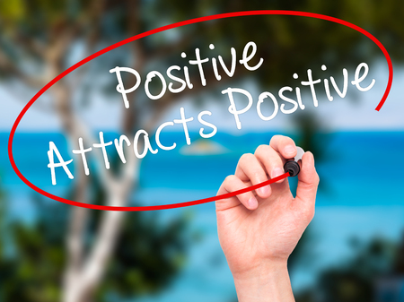 attracts: Man Hand writing Positive Attracts Positive with black marker on visual screen. Isolated on background. Business, technology, internet concept. Stock Photo Stock Photo