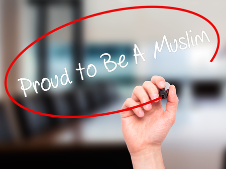 devout: Man Hand writing Proud to Be A Muslim with black marker on visual screen. Isolated on office. Business, technology, internet concept. Stock Photo