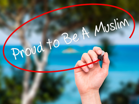 devout: Man Hand writing Proud to Be A Muslim with black marker on visual screen. Isolated on nature. Business, technology, internet concept. Stock Photo