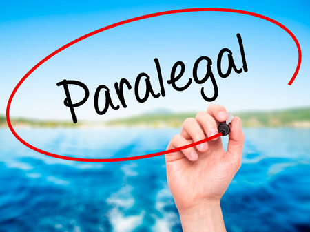 paralegal: Man Hand writing Paralegal with black marker on visual screen. Isolated on nature. Business, technology, internet concept. Stock Photo