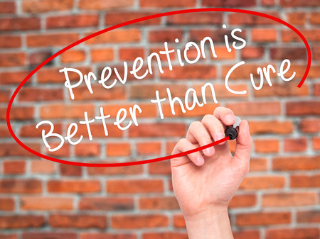 cure prevention: Man Hand writing Prevention is Better than Cure with black marker on visual screen. Isolated on bricks. Business, technology, internet concept. Stock Photo