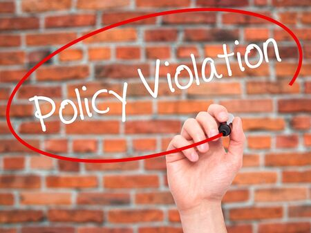 violation: Man Hand writing Policy Violation with black marker on visual screen. Isolated on bricks. Business, technology, internet concept. Stock Photo Stock Photo