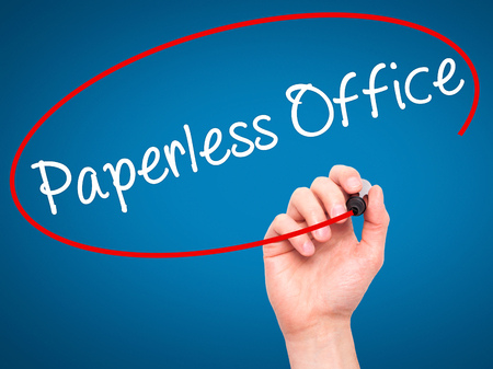 paperless: Man Hand writing Paperless Office  with black marker on visual screen. Isolated on blue. Business, technology, internet concept. Stock Photo