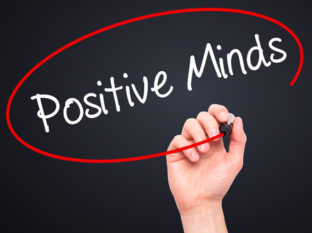 open minded: Man Hand writing Positive Minds with black marker on visual screen. Isolated on black. Business, technology, internet concept. Stock Photo Stock Photo