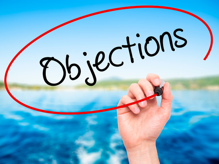 objections: Man Hand writing Objections  with black marker on visual screen. Isolated on nature. Business, technology, internet concept. Stock Photo