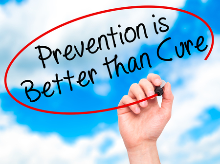 cure prevention: Man Hand writing Prevention is Better than Cure with black marker on visual screen. Isolated on sky. Business, technology, internet concept. Stock Image