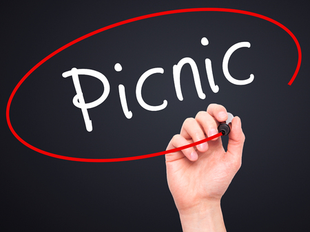 pic nic: Man Hand writing Picnic with black marker on visual screen. Isolated on black. Business, technology, internet concept. Stock Photo Stock Photo