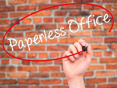 paperless: Man Hand writing Paperless Office  with black marker on visual screen. Isolated on bricks. Business, technology, internet concept. Stock Photo Stock Photo