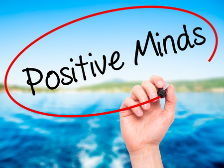 open minded: Man Hand writing Positive Minds with black marker on visual screen. Isolated on nature. Business, technology, internet concept. Stock Photo Stock Photo