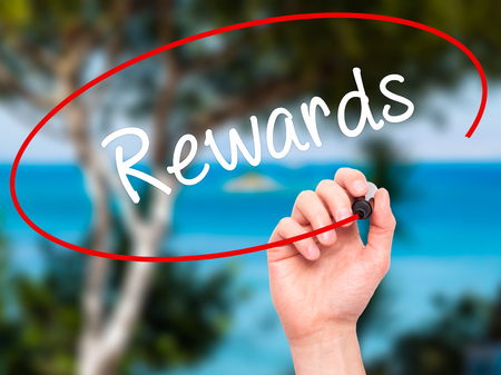 payoff: Man Hand writing Rewards with black marker on visual screen. Isolated on nature. Business, technology, internet concept. Stock Photo