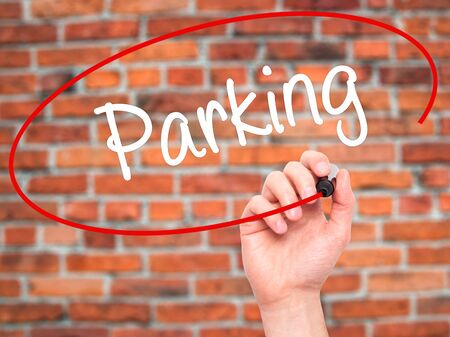 multi story car park: Man Hand writing Parking with black marker on visual screen. Isolated on bricks. Business, technology, internet concept. Stock Photo Stock Photo