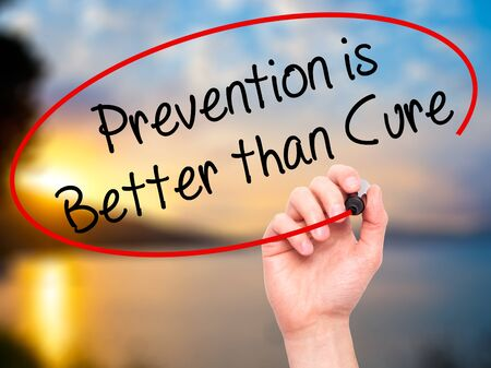 cure prevention: Man Hand writing Prevention is Better than Cure with black marker on visual screen. Isolated on nature. Business, technology, internet concept. Stock Photo Stock Photo