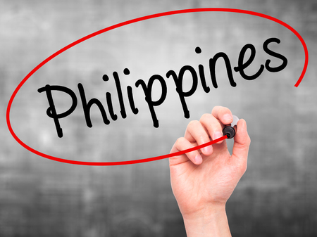 underdeveloped: Man Hand writing Philippines with black marker on visual screen. Isolated on grey. Business, technology, internet concept. Stock Photo