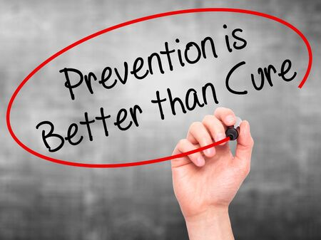 cure prevention: Man Hand writing Prevention is Better than Cure with black marker on visual screen. Isolated on grey. Business, technology, internet concept. Stock Photo