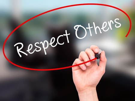 Man Hand writing Respect Others with black marker on visual screen. Isolated on office. Business, technology, internet concept. Stock Photo