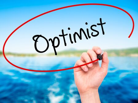 and an optimist: Man Hand writing Optimist  with black marker on visual screen. Isolated on nature. Business, technology, internet concept. Stock Photo