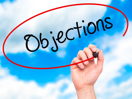 objections: Man Hand writing Objections  with black marker on visual screen. Isolated on sky. Business, technology, internet concept. Stock Photo