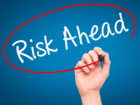 risk ahead: Man Hand writing Risk Ahead with black marker on visual screen. Isolated on blue. Business, technology, internet concept. Stock Image