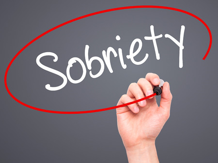 sobriety: Man Hand writing Sobriety with black marker on visual screen. Isolated on grey. Business, technology, internet concept. Stock Photo Stock Photo