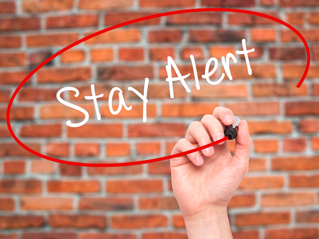 safety slogan: Man Hand writing Stay Alert with black marker on visual screen. Isolated on bricks. Business, technology, internet concept. Stock Photo Stock Photo