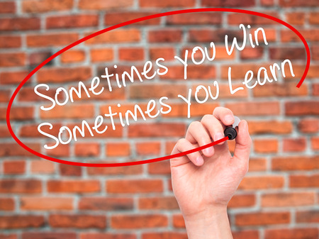 capable of learning: Man Hand writing Sometimes you Win Sometimes you Learn  with black marker on visual screen. Isolated on bricks. Business, technology, internet concept. Stock Photo Stock Photo