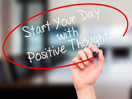 positiveness: Man Hand writing Start your Dat with Positive Thoughts with black marker on visual screen. Isolated on office. Business, technology, internet concept. Stock Photo