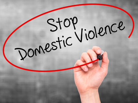 Man Hand writing  Stop Domestic Violence with black marker on visual screen. Isolated on grey. Business, technology, internet concept. Stock Photo